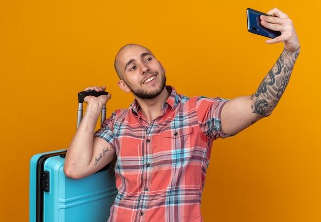Homem jovem viajante sorridente segurando mala e tirando selfie no telefone isolado na parede laranja com espaço de cópia