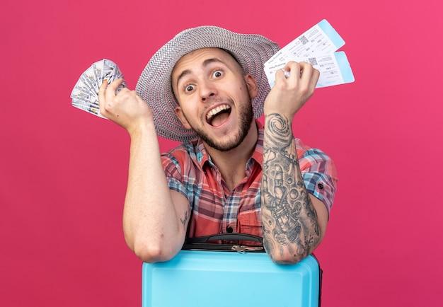 Homem jovem viajante surpreso com chapéu de praia de palha segurando passagens aéreas e dinheiro em pé atrás de uma mala, isolado na parede rosa com espaço de cópia