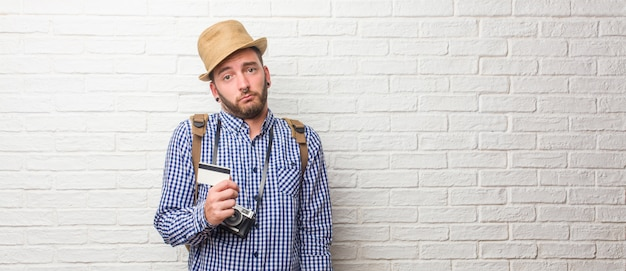 Homem jovem viajante usando mochila e uma câmera vintage, duvidando e encolher os ombros