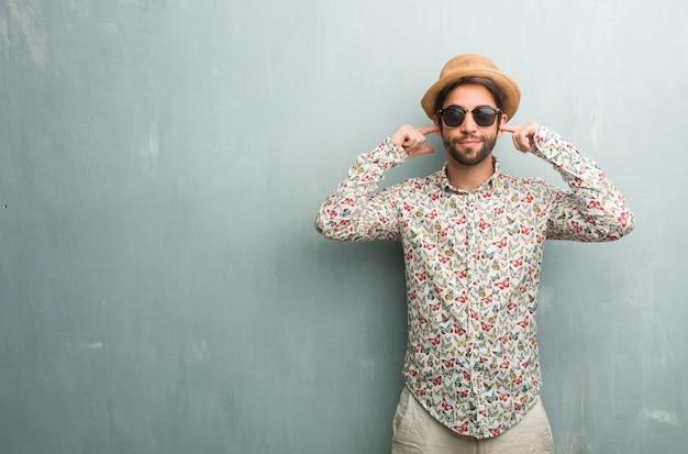 Homem jovem viajante vestindo uma camisa colorida, cobrindo as orelhas com as mãos