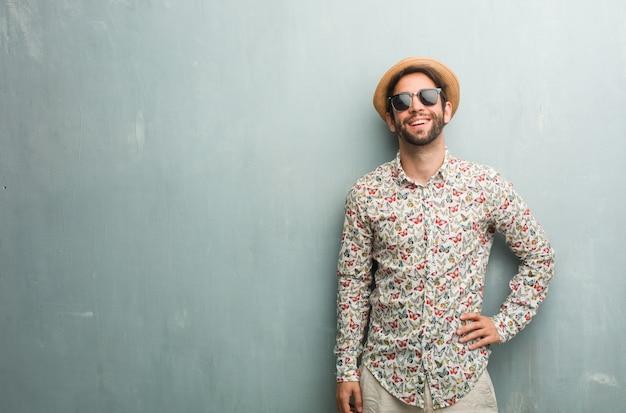 Homem jovem viajante vestindo uma camisa colorida com as mãos nos quadris, em pé, relaxado e sorridente, muito positivo e alegre