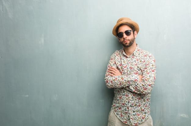 Homem jovem viajante vestindo uma camisa colorida, cruzando os braços, séria e imponente, sentindo-se confiante e mostrando poder