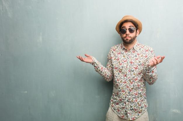 Homem jovem viajante vestindo uma camisa colorida, duvidando e encolhendo os ombros, conceito de indecisão e insegurança, incerto sobre algo