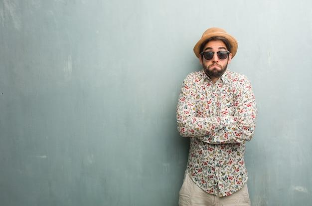 Homem jovem viajante vestindo uma camisa colorida, duvidando e encolher os ombros