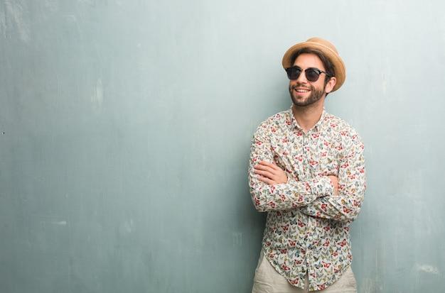 Homem jovem viajante vestindo uma camisa colorida, olhando para cima, pensando em algo divertido e ter uma idéia