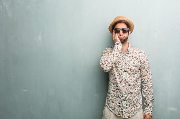 Homem jovem viajante vestindo uma camisa colorida, preocupado e oprimido, esquecido