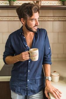 Homem jovem, xícara café segurando, olhando