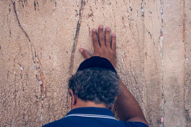 Homem judeu ortodoxo orando com fortes emoções perto das pedras do muro das lamentações, uma das principais relíquias judaicas antigas. parte traseira da cabeça de um velho que toca a parede de calcário e reza.