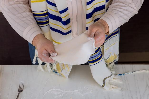 Homem judeu ortodoxo se prepara para o dia de feriado judaico em preparação de matzá casher plana feita à mão