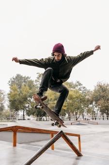 Homem lá fora com skate no parque da cidade