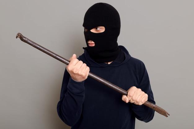 Homem ladrão com pé-de-cabra à mão desvia o olhar