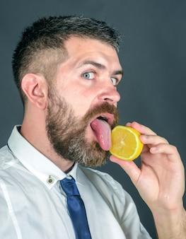 Homem lambe limão vegetariano saúde e bem-estar frutas e alimentos orgânicos saudáveis dieta e fitness vitamina cítrica no hipster em preto