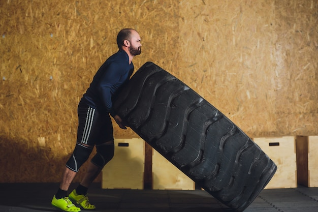 Homem lançando pneu pesado no ginásio.