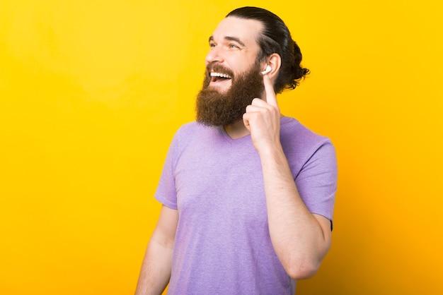 Homem largo e sorridente está animado com seus novos fones de ouvido.