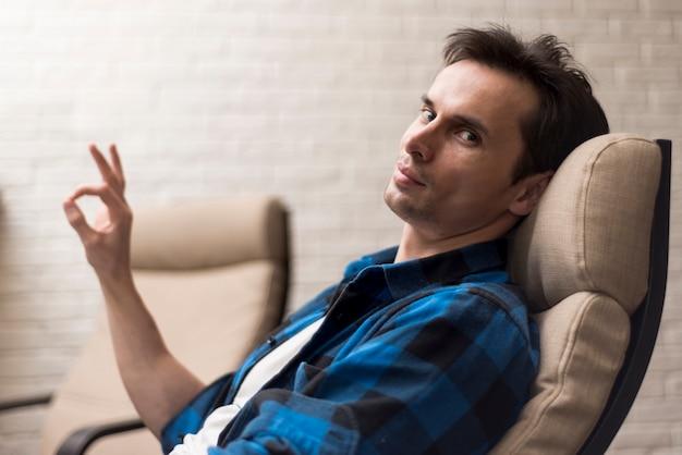 Homem lateral sentado e aprovando