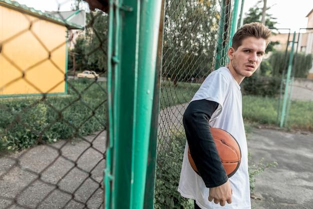 Homem lateralmente com uma bola de basquete