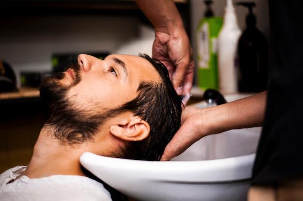 Homem lateralmente, recebendo uma lavagem do cabelo