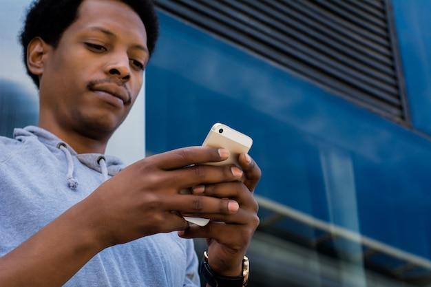 Homem latin novo que datilografa em seu telefone.