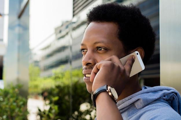 Homem latin novo que fala no telefone móvel fora.