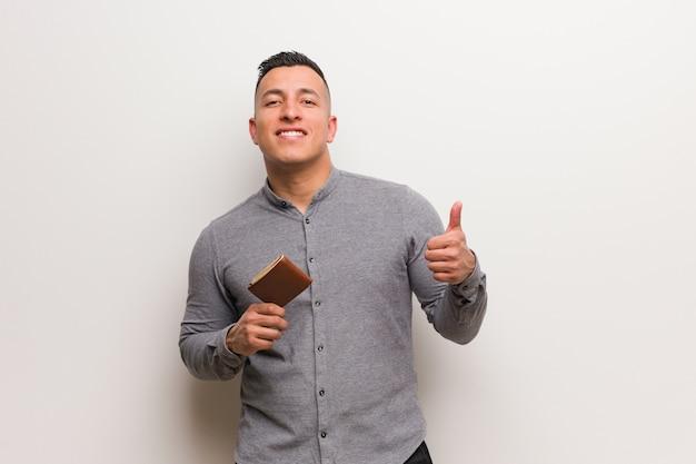 Homem latin novo que prende uma carteira que sorri e que levanta o polegar acima
