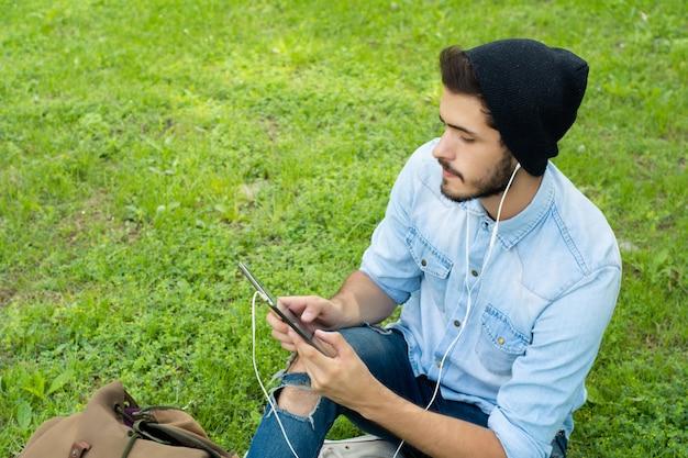 Homem latin novo que usa a tabuleta ao ar livre.