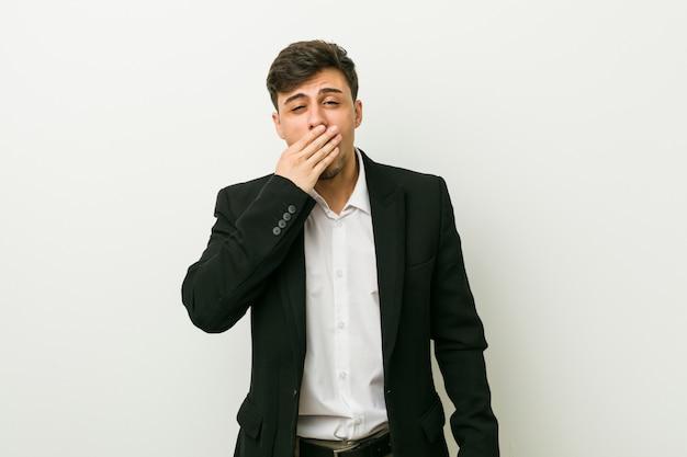 Homem latino-americano do negócio novo que boceja mostrando um gesto cansado que cobre a boca com a mão.
