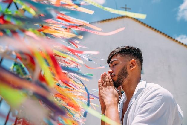 Homem latino-americano fazendo um pedido com fitas brasileiras na cerca de uma igreja em arraial d'ajuda, bahia, brasil