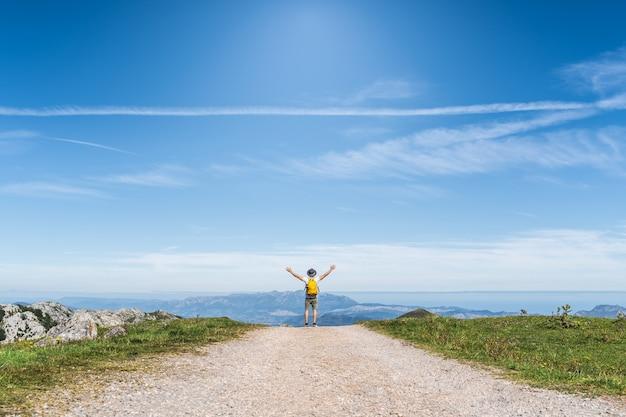 Homem latino-americano mãos para cima caminhadas na montanha