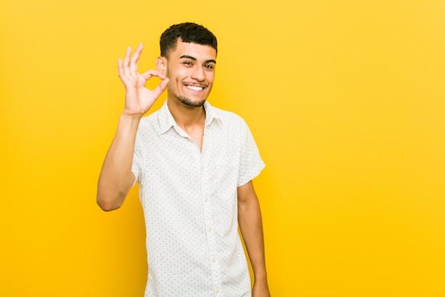 Homem latino-americano novo alegre e seguro mostrando o gesto aprovado.