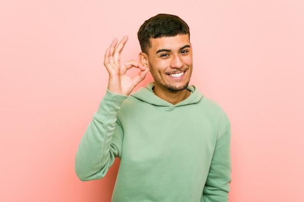Homem latino-americano novo do esporte alegre e confiável mostrando o gesto aprovado.