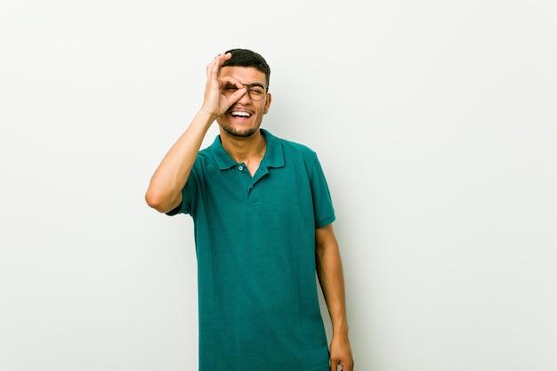 Homem latino-americano novo entusiasmado mantendo o gesto aprovado no olho.