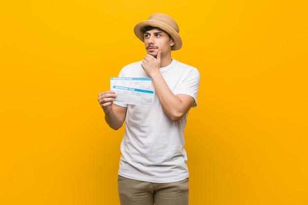Homem latino-americano novo guardando passagens aéreas que olham lateralmente com expressão duvidosa e cética.