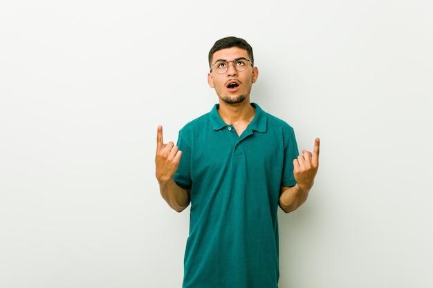 Homem latino-americano novo que aponta de cabeça com boca aberta.