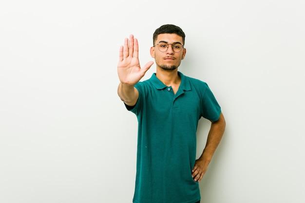 Homem latino-americano novo que está com a mão estendida que mostra o sinal de parada, impedindo-o.