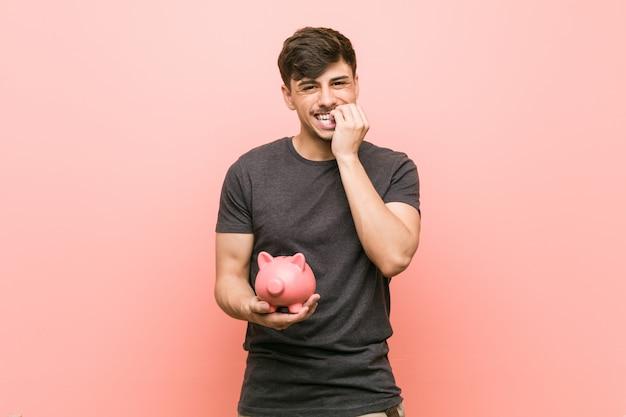 Homem latino-americano novo que guarda as unhas cortantes do mealheiro, nervosas e muito ansiosas.