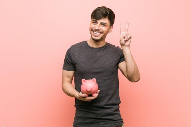 Homem latino-americano novo que guarda o mealheiro que mostra o sinal da vitória e que sorri amplamente.