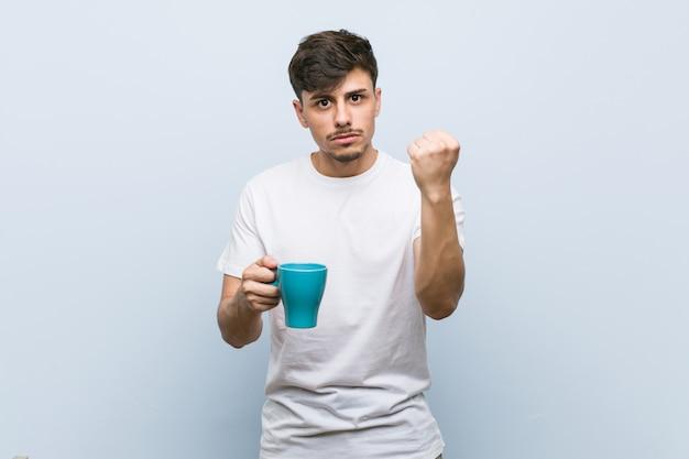 Homem latino-americano novo que guarda um copo que mostra o punho à câmera, expressão facial agressiva.