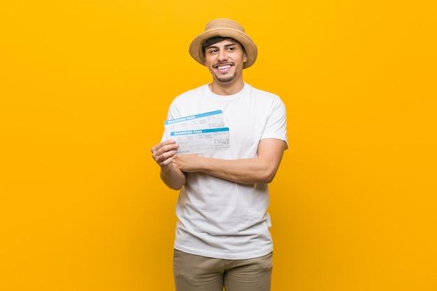 Homem latino-americano novo que guarda um sorriso das passagens aéreas seguro com braços cruzados.