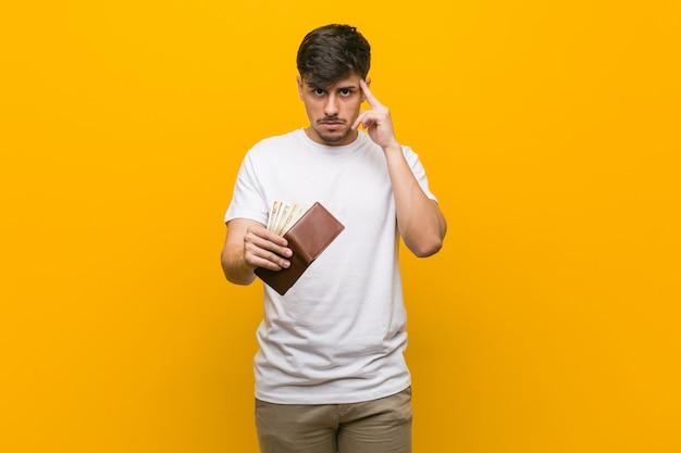 Homem latino-americano novo que guarda uma carteira que aponta seu templo com o dedo, pensando, focalizado em uma tarefa.
