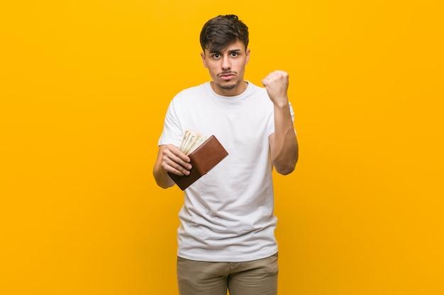 Homem latino-americano novo que guarda uma carteira que mostra o punho à câmera, expressão facial agressiva.
