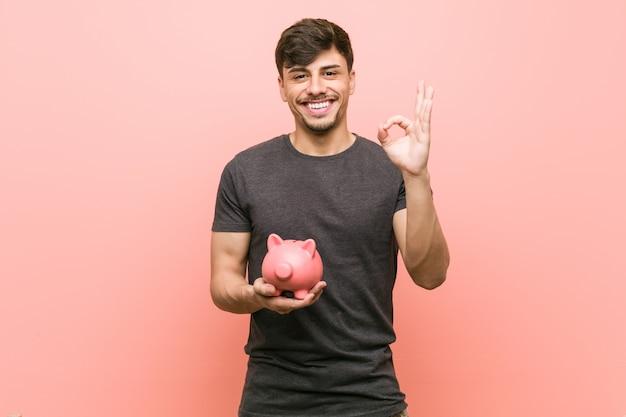 Homem latino-americano novo que mantém o mealheiro alegre e seguro mostrando o gesto aprovado.