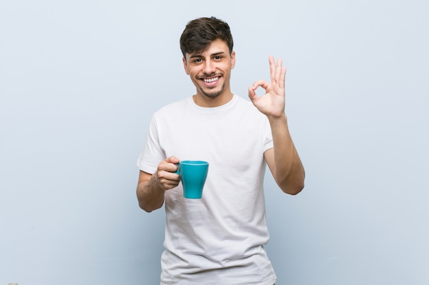 Homem latino-americano novo que mantém um copo alegre e seguro mostrando o gesto aprovado.