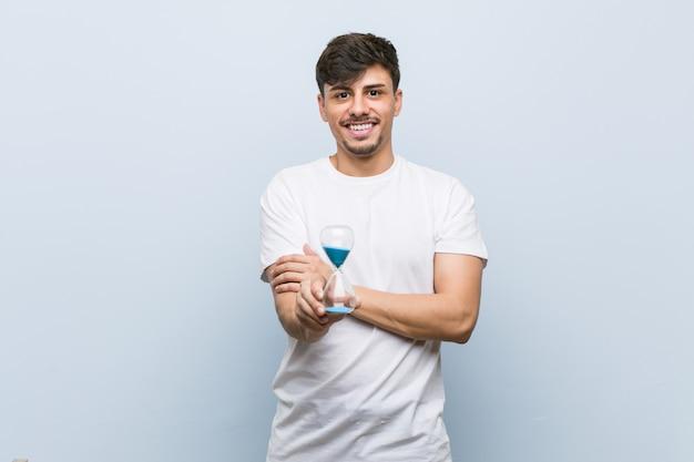 Homem latino-americano novo que mantém um sorriso da ampulheta seguro com braços cruzados.