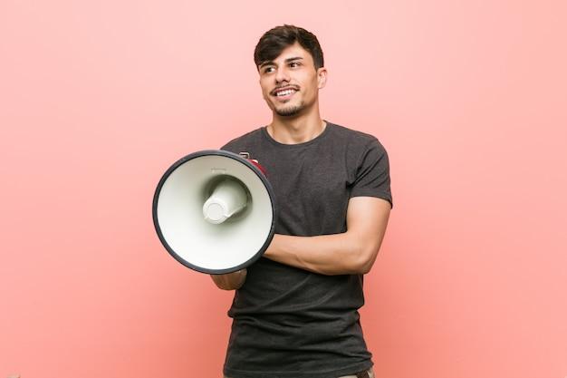 Homem latino-americano novo que mantém um sorriso do megafone seguro com braços cruzados.