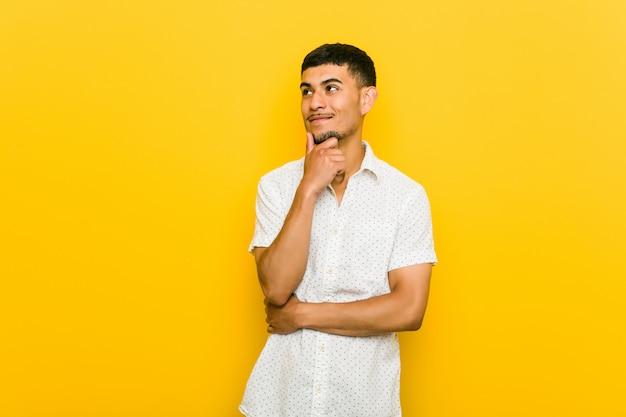 Homem latino-americano novo que olha lateralmente com expressão duvidosa e cética.