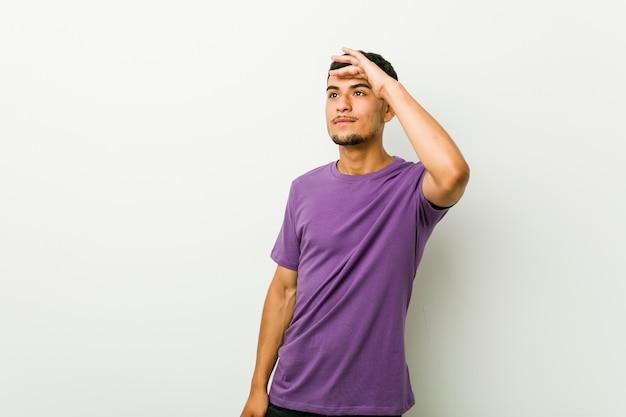 Homem latino-americano novo que olha longe mantendo a mão na testa.
