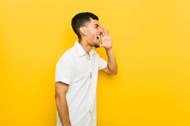 Homem latino-americano novo que shouting e que prende a palma perto da boca aberta.
