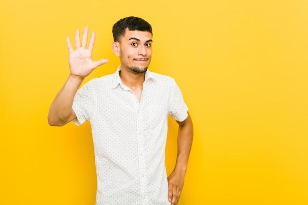 Homem latino-americano novo que sorri mostrando alegre número cinco com dedos.