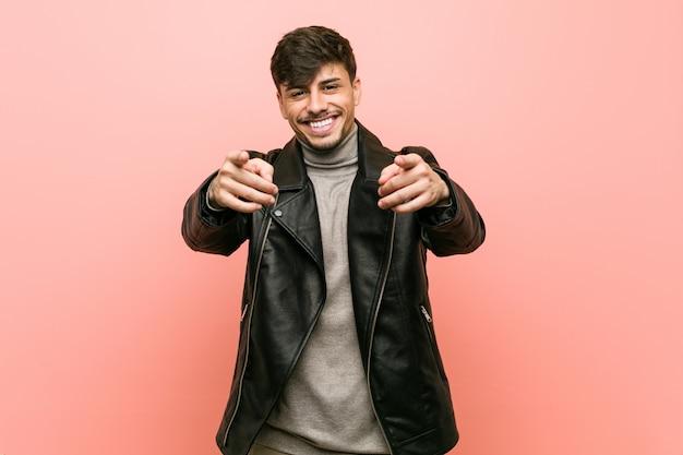 Homem latino-americano novo que veste um sorriso alegre da jaqueta de couro que aponta à parte dianteira.