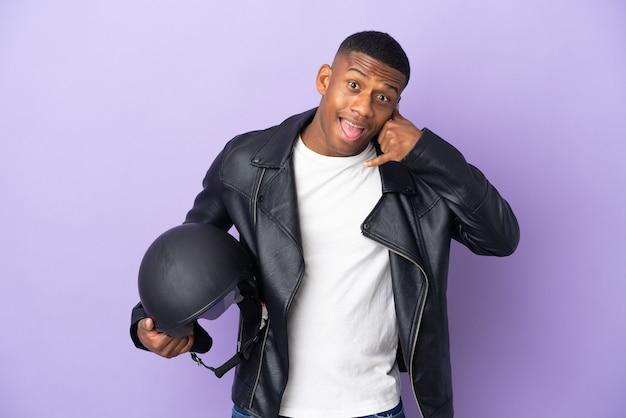 Homem latino com um capacete de motocicleta isolado em roxo, fazendo gesto de telefone. ligue-me de volta sinal